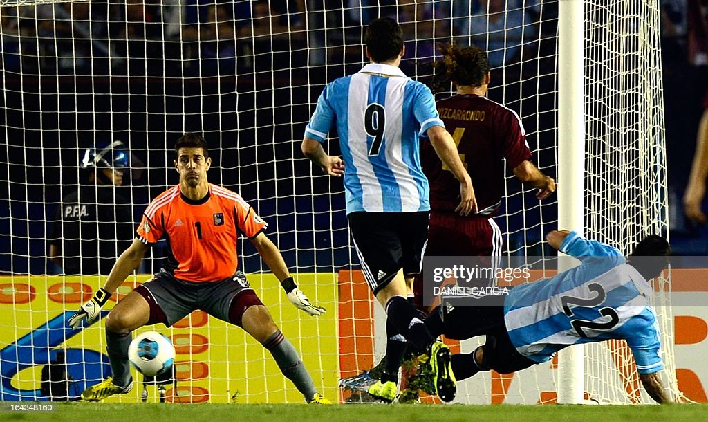 Venezuelan goalkeeper Daniel Hernandez (L) prepares to dive after Argentine forward Ezequiel Lavezzi (R) shot the ball during their FIFA World Cup Brazil 2014 South American qualifying football match in Buenos Aires, Argentina on March 22, 2013.