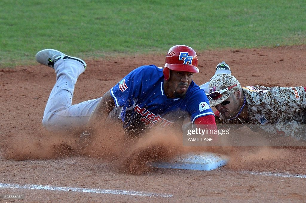 Venezuelan infielder Felix Perez (R) makes the out on first base against Puerto Rico's Henry Ramos during their 2016 Caribbean baseball series game on February 6, 2016 in Santo Domingo, Dominican Republic. AFP PHOTO/YAMIL LAGE / AFP / YAMIL LAGE