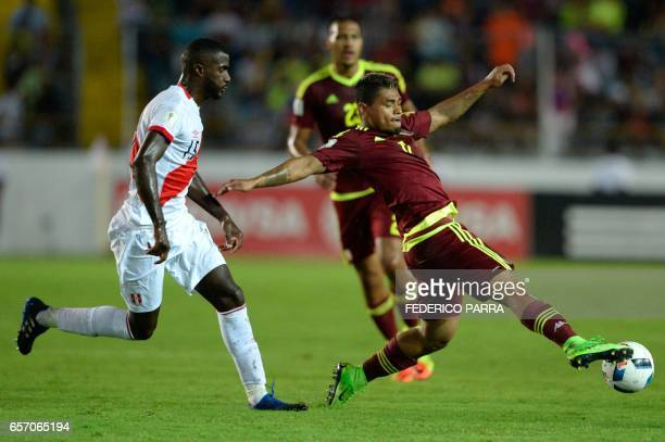 Venezuelan Josef Martinez controls the ball next to Peru's Cristian Ramos during their 2018 FIFA World Cup qualifier football match in Maturin...