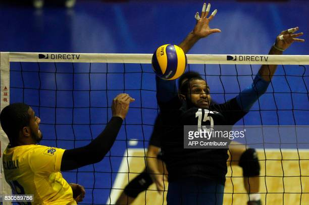 Venezuelan Luis Arias try to block the smash of Brazilian Lucarelli during their Men's South American Volleyball Championship final in Santiago on...