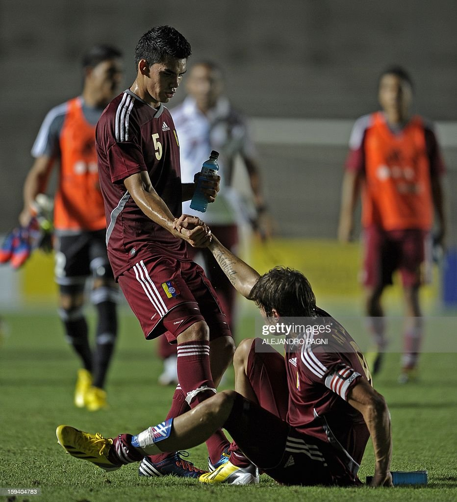 Venezuelan midfielder Gilbert Guerra (L) helps his teammate forward Manuel Arteaga at the end their South American U-20 Championship Group B football match against Ecuador, at Bicentenario stadium in San Juan, Argentina, on January 12, 2013. Four South American teams will qualify for the FIFA U-20 World Cup Turkey 2013. Venezuela won by 1-0.