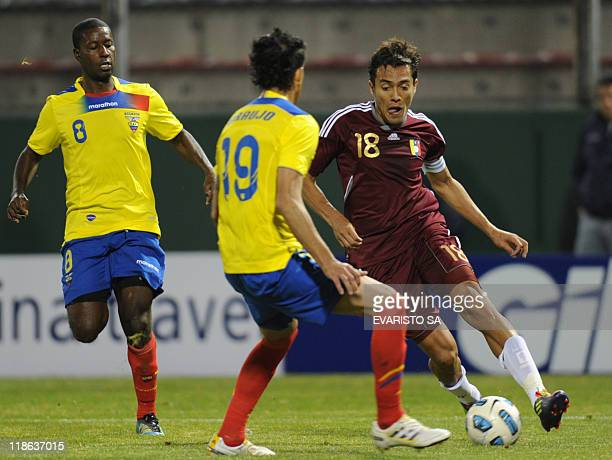Venezuelan midfielder Juan Arango vies for the ball with Ecuadorean defender Norberto Araujo and midfielder Edison Mendez during a 2011 Copa America...
