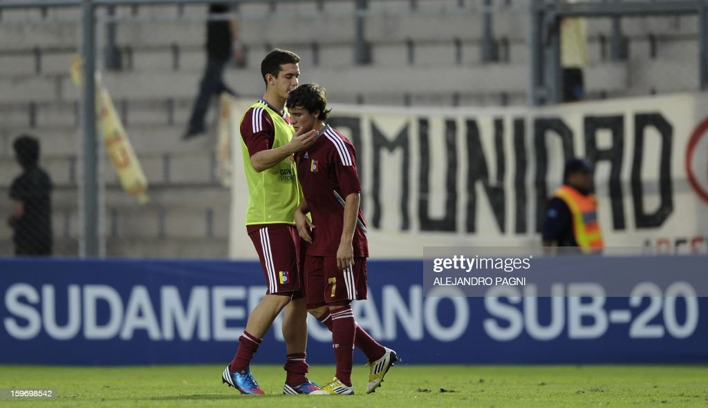 Venezuelan midfielder Robert Hernandez (R) is comforted by a teammate at the end of their South American U-20 Championship Group B football match against Uruguay, at Bicentenario stadium in San Juan, Argentina, on January 18, 2013. Four teams will qualify for the Turkey 2013 FIFA U-20 World Cup.