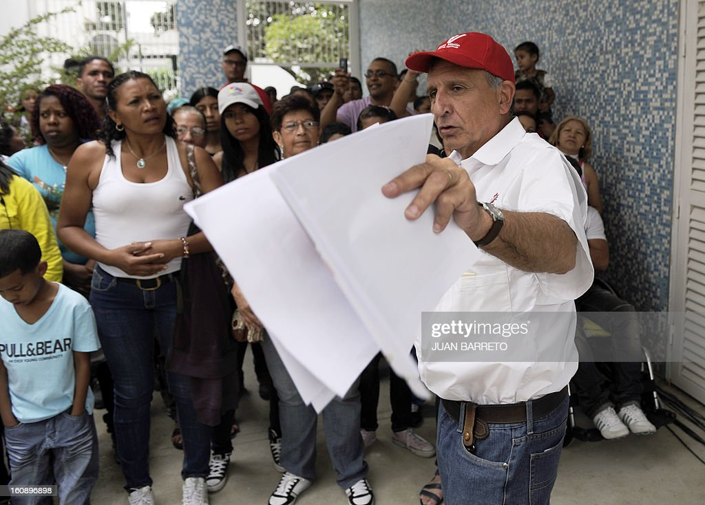 """Venezuelan Minister for the Revolutionary Transformation of Greater Caracas, Francisco """"Farruco"""" Sesto (R) talks to the new owners of homes delivered by the National Government, in Caracas on February 7, 2013. AFP PHOTO/Juan Barreto"""