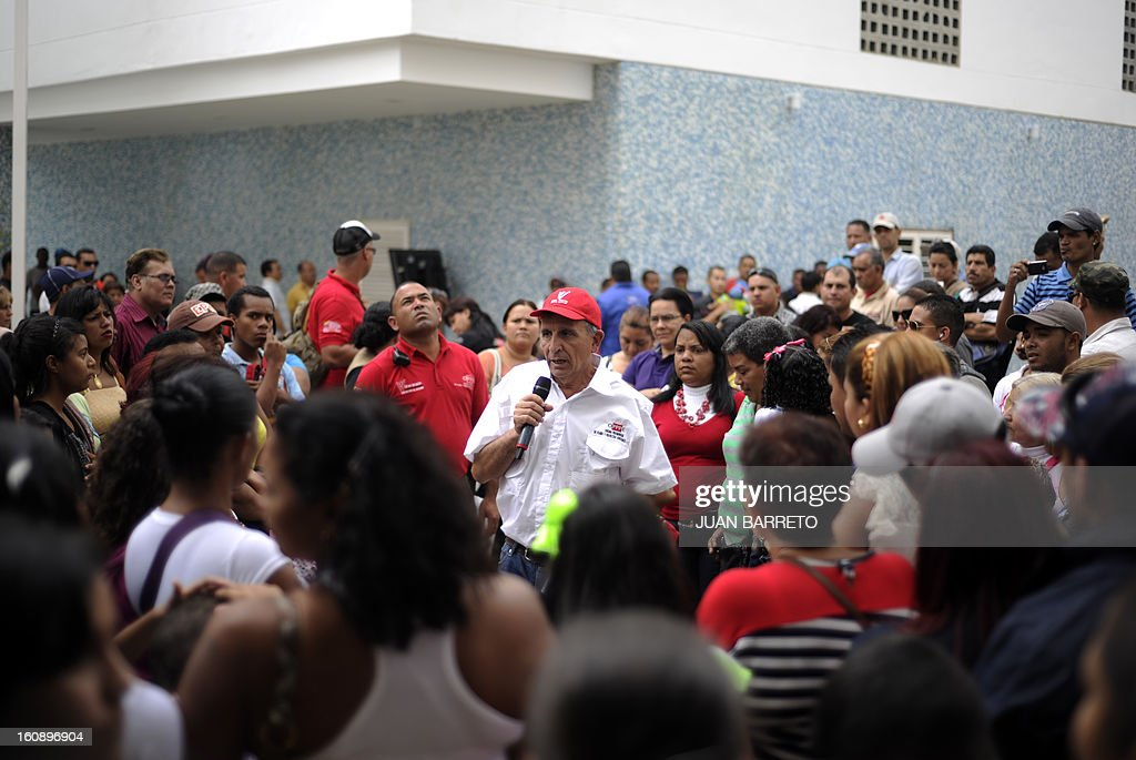 "Venezuelan Minister for the Revolutionary Transformation of Greater Caracas, Francisco ""Farruco"" Sesto (C) talks with the new owners of homes delivered by the National Government, in Caracas on February 7, 2013. AFP PHOTO/Juan Barreto"