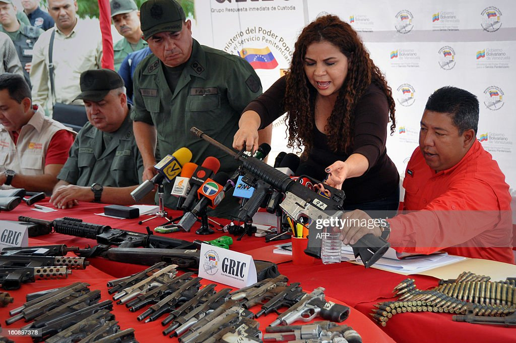Venezuelan Minister of Correctional Services Iris Varela (2-R) shows a rifle during a press conference in Barquisimeto, Venezuela on February 7, 2013. A total of 106 weapons, including rifles and submachine guns, 8568 ammunitions and a dozen grenades were seized by Venezuelan authorities after the eviction of Uribana prison in Lara state (northwest), where 58 people were killed during a riot two weeks ago. AFP PHOTO/Dedwinson Alvarez