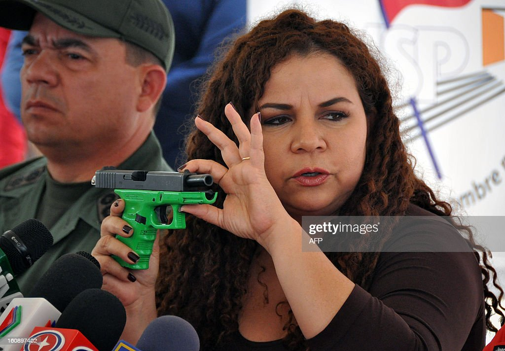 Venezuelan Minister of Correctional Services Iris Varela shows a handgun during a press conference in Barquisimeto, Venezuela on February 7, 2013. A total of 106 weapons, including rifles and submachine guns, 8568 ammunitions and a dozen grenades were seized by Venezuelan authorities after the eviction of Uribana prison in Lara state (northwest), where 58 people were killed during a riot two weeks ago. AFP PHOTO/Dedwinson Alvarez