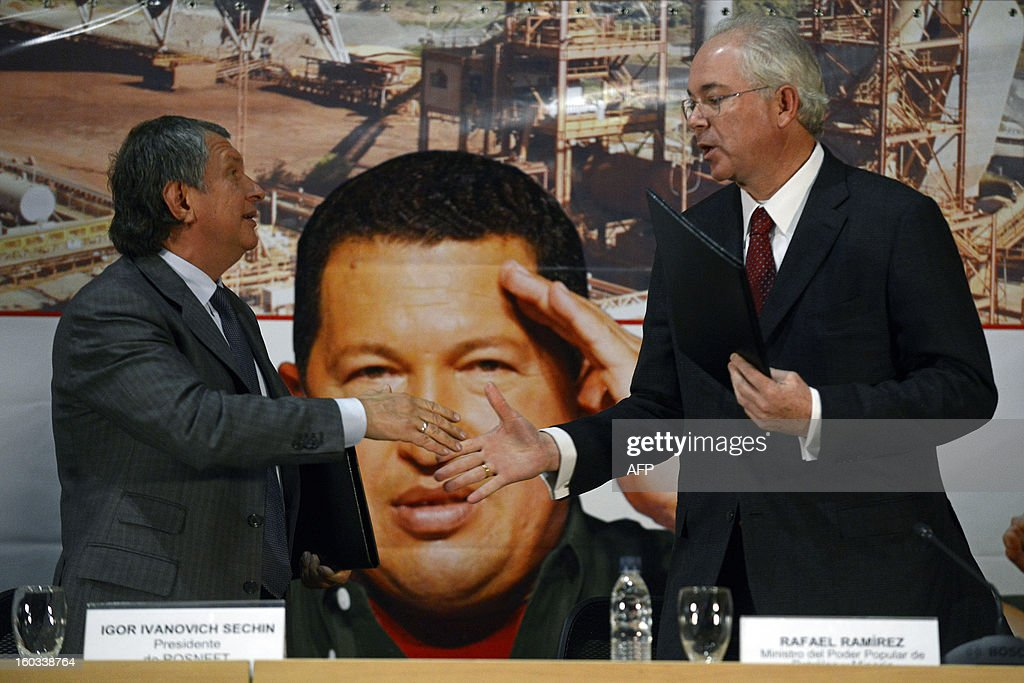 Venezuelan Minister of Oil and Mining and president of state-owned oil company PDVSA Rafael Ramirez (R) shakes hands with the the CEO of Russian state-owned oil company ROSNEFT, Igor Ivanovich Sechin (L) during a meeting to evaluate the development of joint projects in the area of energy and hydrocarbons, in Caracas on January 29, 2013. AFP PHOTO/ Leo RAMIREZ