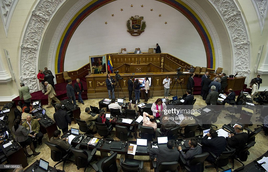 Venezuelan National Assembly president, Diosdado Cabello (C-back), and Vice-President Dario Vivas (L-back) are seen before a session in Caracas on January 8, 2013. Cabello announced on January 8, 2013, that due to health reasons, Venezuelan President Hugo Chavez will not be able to take the oath to be sworn in for a fourth term in office next January 10. AFP PHOTO/JUAN BARRETO