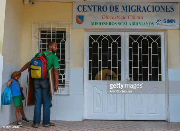 Venezuelan national Ernesto Toro and his son wait to get food and shelter in front of the Migration Center in Cucuta North of the Santander...