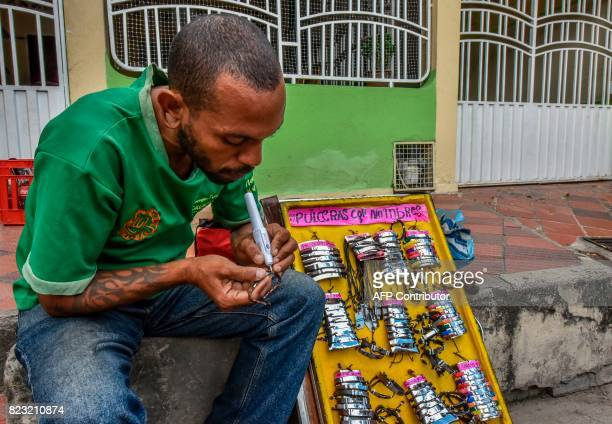Venezuelan national Ernesto Toro make bracelets for sale as he waits to get food and shelter in front of the Migration Center in Cucuta North of the...