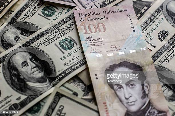 A Venezuelan one hundred bolivar note is arranged for a photograph with US bills in Caracas Venezuela on Sunday Feb 22 2015 A decline in oil revenue...