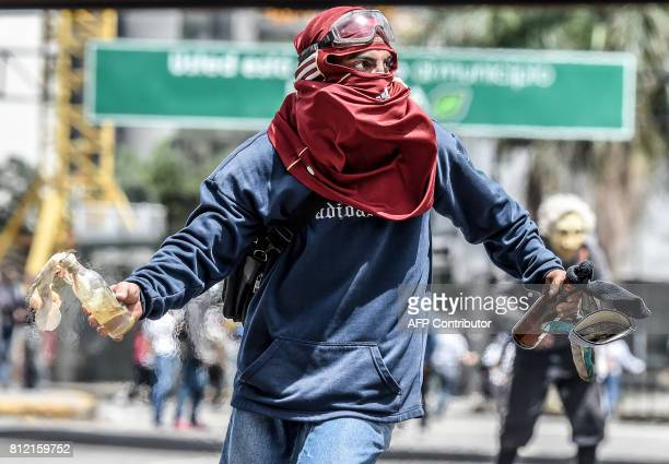 A Venezuelan opposition activist clashes with riot police during a protest against Venezuelan President Nicolas Maduro in Caracas on July 10 2017...