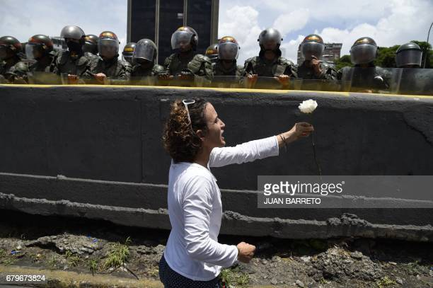 Venezuelan opposition activist offers a flower to members of the Bolivarian National Guard standing guard during a women's march aimed to keep...