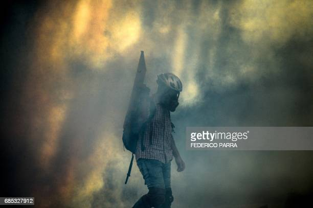 A Venezuelan opposition activist walks amid tear gas during clashes with the police within a rally against the government of President Nicolas Maduro...