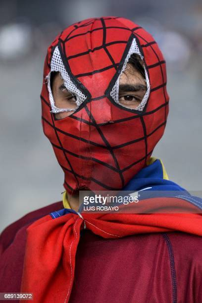 A Venezuelan opposition activist wearing a mask clashes with riot police during a demonstration against Venezuelan President Nicolas Maduro in...