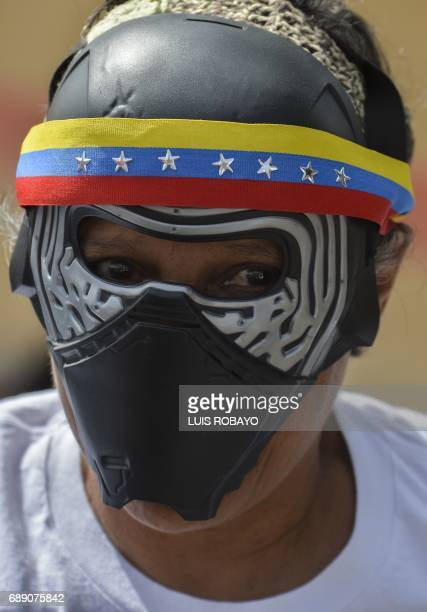 A Venezuelan opposition activist wearing a mask takes part in a religious march for peace in Caracas on May 27 2017 Demonstrations that got underway...