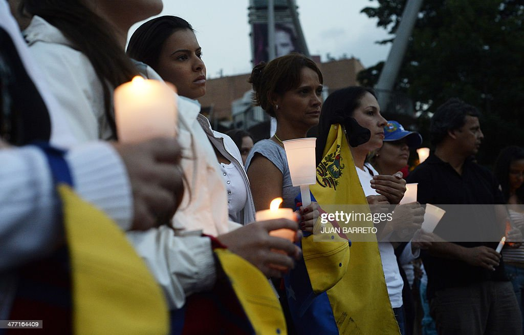 Venezuelan opposition activists and students hold candles during a demonstration against the government of Venezuelan President Nicolas Maduro in Caracas on March 7, 2014.