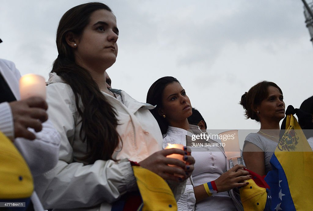 Venezuelan opposition activists and students hold candles during a demonstration against the government of Venezuelan President Nicolas Maduro in Caracas on March 7, 2014. AFP PHOTO /JUAN BARRETO