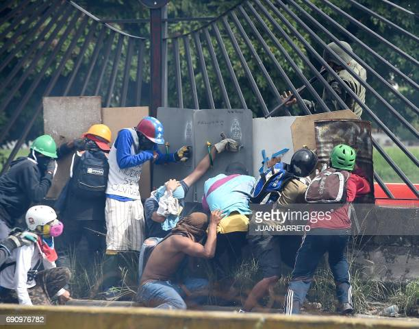 TOPSHOT Venezuelan opposition activists attempt to defilade behind a wall from a National Guard riot policeman shooting rubber bullets at them during...