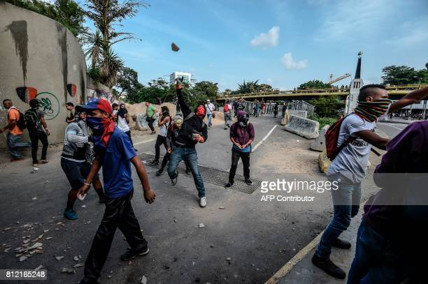 TOPSHOT Venezuelan opposition activists clash with riot police during a protest against Venezuelan President Nicolas Maduro in Caracas on July 10...