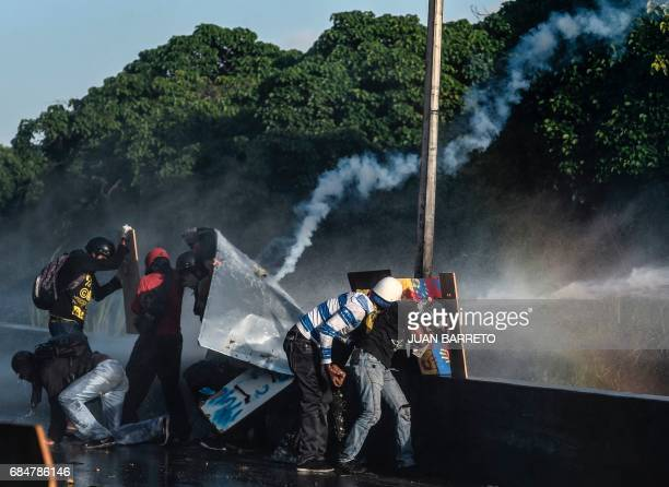 Venezuelan opposition activists clash with the riot police during a rally against the government of President Nicolas Maduro in Caracas on May 18...