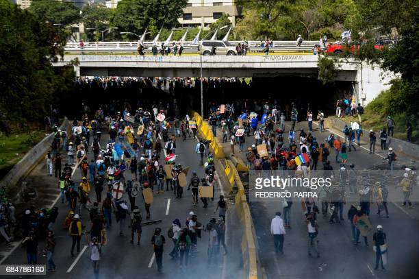 Venezuelan opposition activists clash with the riot police during a protest against the government of President Nicolas Maduro in Caracas on May 18...
