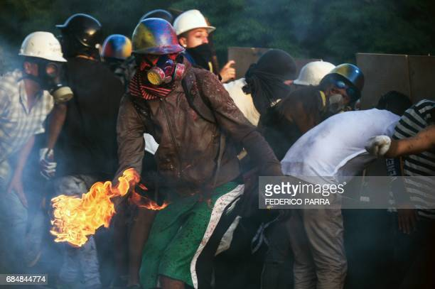 TOPSHOT Venezuelan opposition activists clash with the riot police during a rally against the government of President Nicolas Maduro in Caracas on...