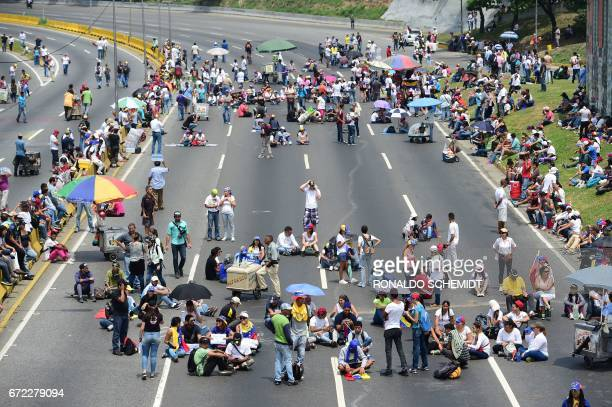 TOPSHOT Venezuelan opposition activists organize a sitin to block the Francisco Fajardo motorway in Caracas on April 24 2017 Protesters plan Monday...