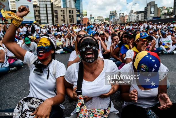 TOPSHOT Venezuelan opposition activists take part in a march aimed to keep pressure on President Nicolas Maduro whose authority is being increasingly...