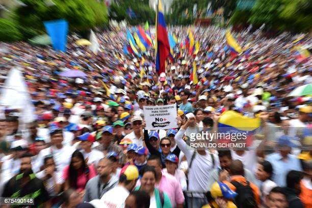 TOPSHOT Venezuelan opposition activists taks part in a march against President Nicolas Maduro in Caracas on May 1 2017 Security forces in riot vans...