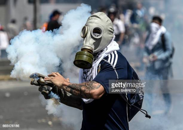 A Venezuelan opposition activists wears a gas mask during clahes with the police within a protest against the government of President Nicolas Maduro...