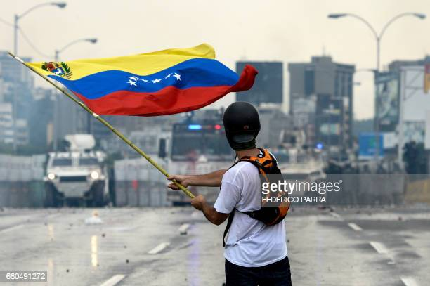Venezuelan opposition demonstrator waves a flag at the riot police in a clash during a protest against President Nicolas Maduro in Caracas on May 8...