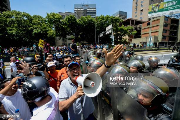 Venezuelan opposition deputy Ismael Garcia harangues the demonstrators in front of a line of iot police during a protest against President Nicolas...