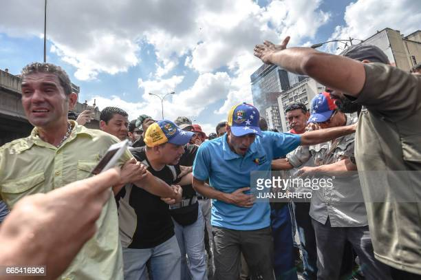 Venezuelan opposition leader and former presidential candidate Henrique Capriles reacts to tear gas shot by the police during protests against the...