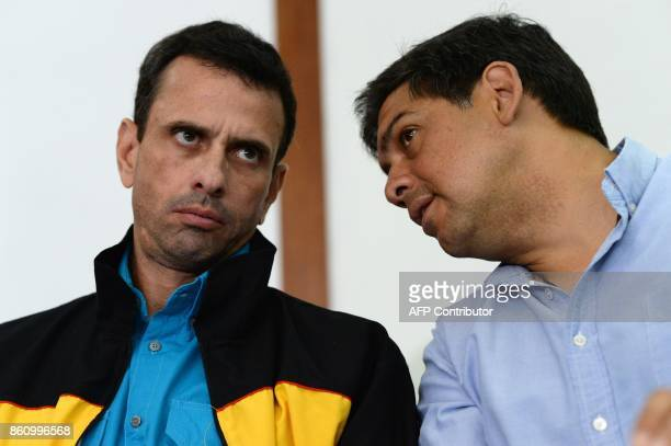 Venezuelan opposition leader and Miranda state governor Henrique Capriles listen tos candidate Carlos Ocariz during a press conference in Caracas on...