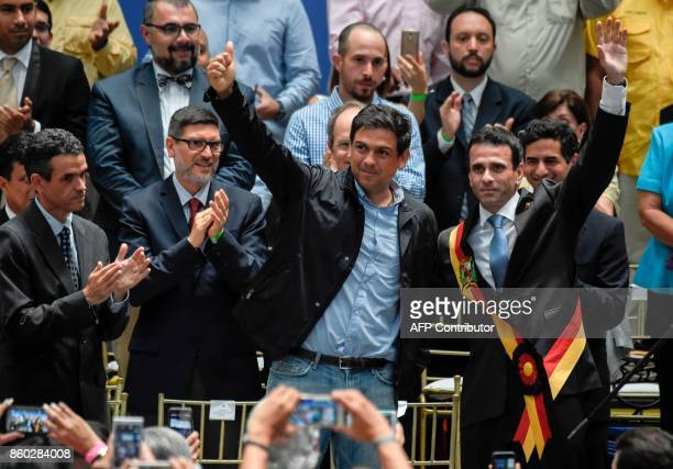 Venezuelan opposition leader Henrique Capriles and Miranda state gubernatorial candidate Carlos Ocariz wave during a rally in Caracas on October 11...