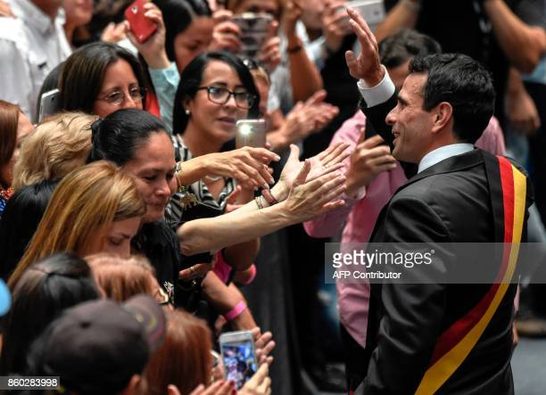 Venezuelan opposition leader Henrique Capriles is greeted by supporters during a rally in Caracas on October 11 2017 Venezuelans will go to...