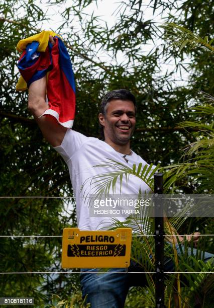 Venezuelan opposition leader Leopoldo Lopez displays a Venezuelan national flag as he greets supporters gathering outside his house in Caracas after...