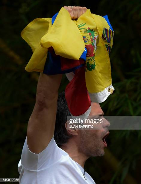 Venezuelan opposition leader Leopoldo Lopez displays the Venezuelan national flag as he greets supporters gathering outside his house in Caracas...