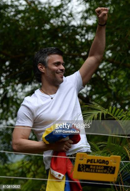Venezuelan opposition leader Leopoldo Lopez greets supporters gathering outside his house in Caracas after he was released from prison and placed...