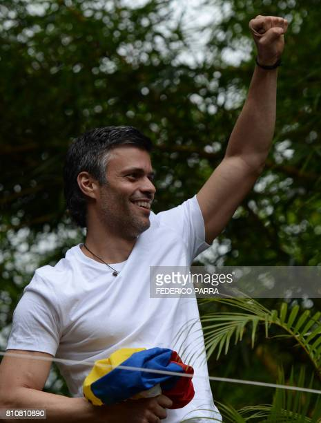 Venezuelan opposition leader Leopoldo Lopez holds a Venezuelan national flag against his chest as he greets supporters gathering outside his house in...