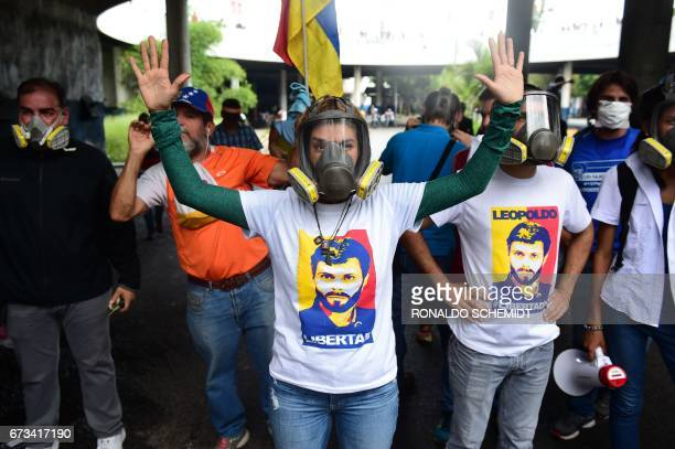 Venezuelan opposition leader Lilian Tintori wife of jailed opposition leader Leopoldo Lopez wears a gas mask during clashes with riot police ensueing...