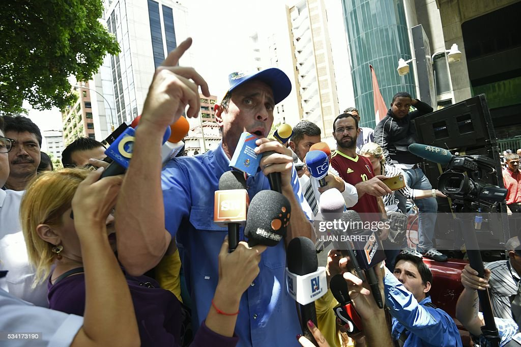Venezuelan opposition leader, Miranda state Governor Henrique Capriles, speaks to the press during a protest outside the Spreme Tribunal of Justice (TSJ) in Caracas on May 25, 2016. Protesters seeking to drive Venezuela's President Nicolas Maduro from office launched fresh street rallies on Wednesday, a test of their strength in a tense political crisis. / AFP / JUAN