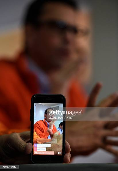 Venezuelan opposition leader Miranda state Governor Henrique Capriles appears on a screen of a mobile phone as he speaks during a press conference in...