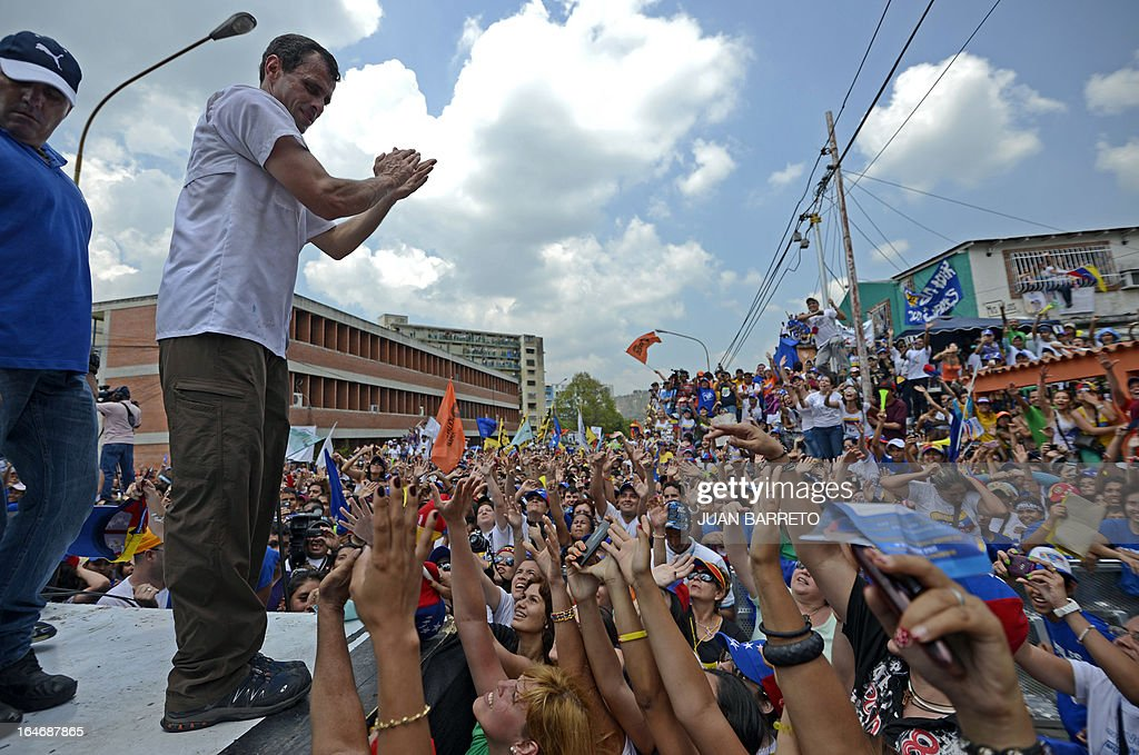 Venezuelan opposition presidential candidate Henrique Capriles (L) greets his supporters during a rally in Valera, Trujillo state, Venezuela on March 26, 2013. Venezuela will elect its new president on April 14, 2013. AFP PHOTO