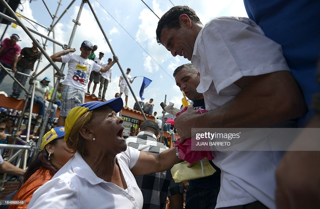 Venezuelan opposition presidential candidate Henrique Capriles (R) is greeted by supporters during a rally in Valera, Trujillo state, Venezuela on March 26, 2013. Venezuela will elect its new president on April 14, 2013. AFP PHOTO