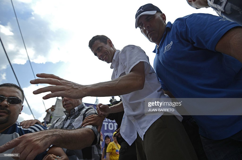 Venezuelan opposition presidential candidate Henrique Capriles (L) waves at his supporters during a rally in Valera, Trujillo state, Venezuela on March 26, 2013. Venezuela will elect its new president on April 14, 2013. AFP PHOTO