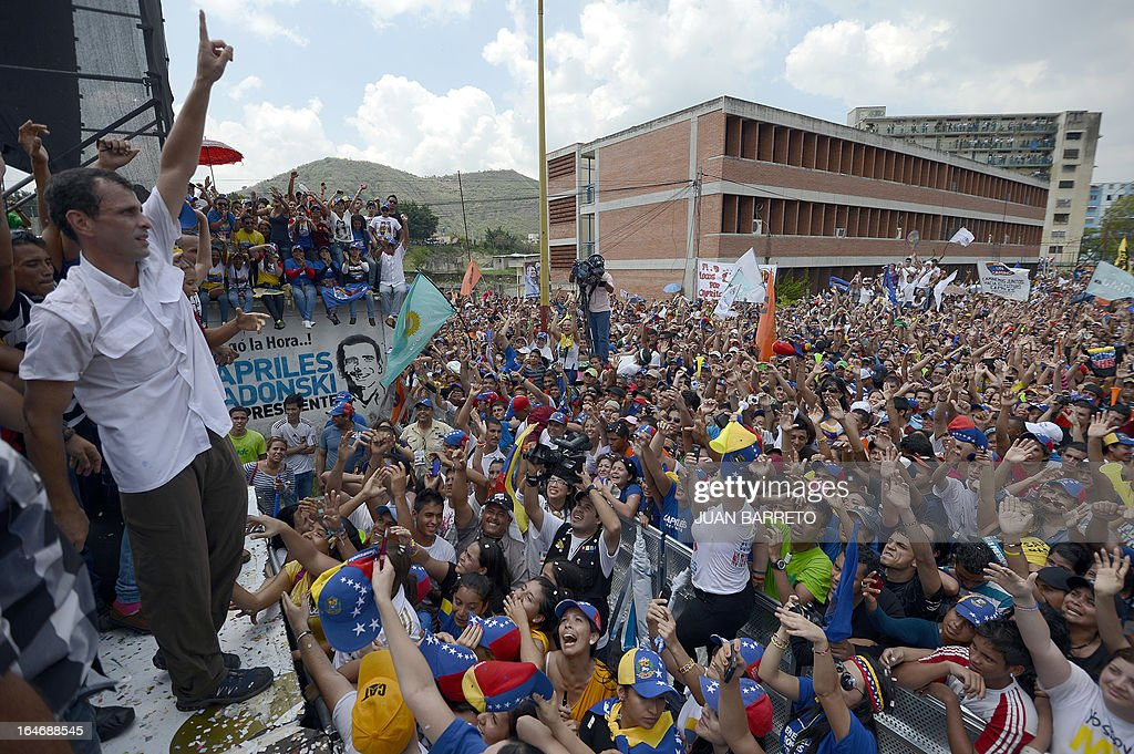 Venezuelan opposition presidential candidate Henrique Capriles (L) waves at his supporters during a rally in Valera, Trujillo state, Venezuela on March 26, 2013. Venezuela will elect its new president on April 14, 2013. AFP PHOTO/JUAN BARRETO