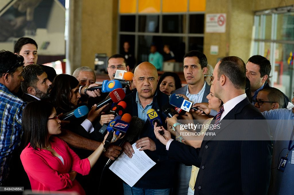 Venezuelan opposition spokesman of the Democratic Unity Roundtable (MUD) Jesus Torrealba (C) speaks with the media at the National Electoral Council in Caracas on June 28, 2016. Opposition leaders in Venezuela said that they have finished the process of authenticating signatures on a petition to recall President Nicolas Maduro, and have enough to hold a referendum on removing him. / AFP / FEDERICO
